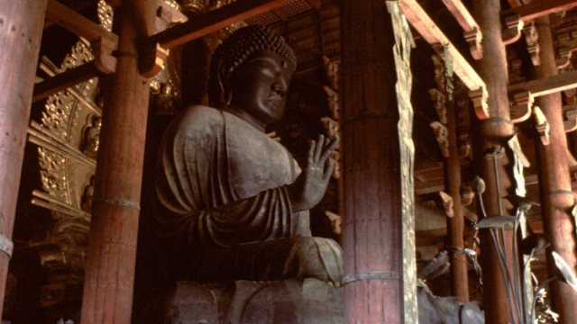 Large sculpture of Gautama Buddha set in timber architecture.