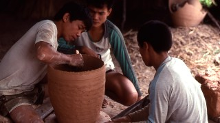 photograph of a man making a clay pot as two other men look on