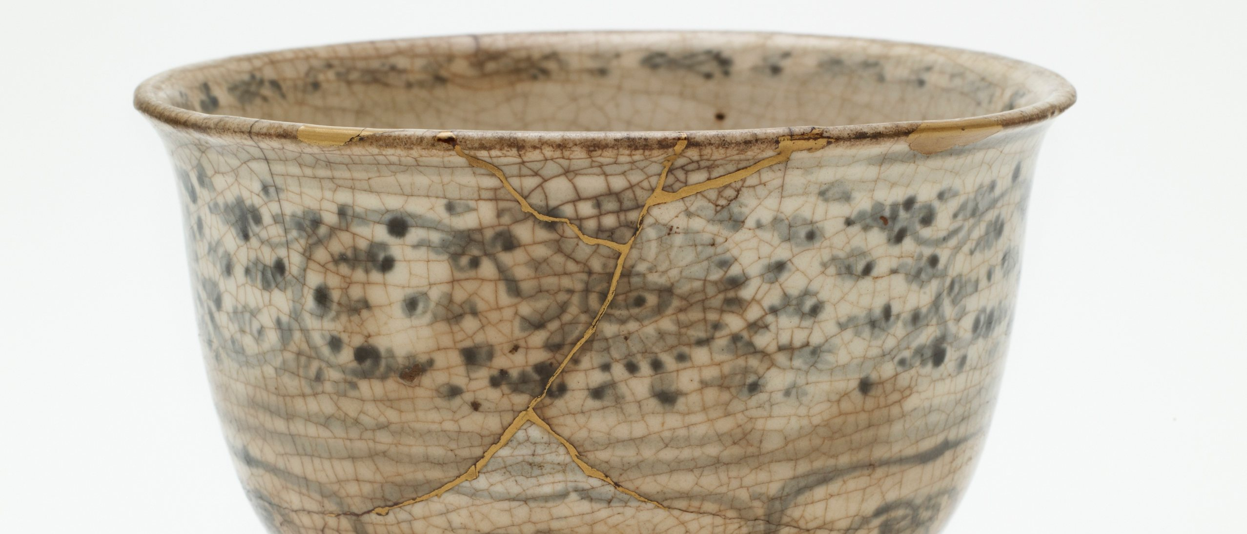 glazed stoneware bowl with painted designs . discolored cracks across surface