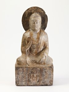 a small limestone buddha, seated, with one hand raised