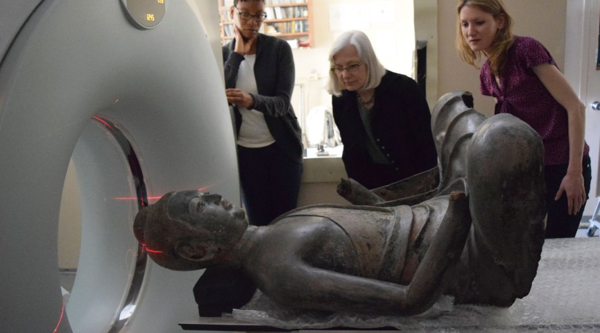Conservators look on as the Freer buddha goes into the CT scanning equipment