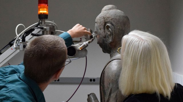scientist and conservator working on a buddha