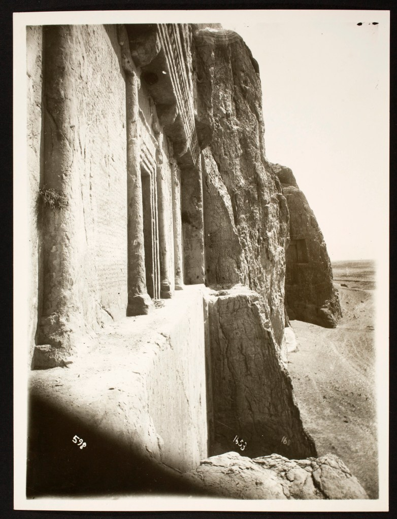 An oblique view of a tomb entrance carved into the face of a cliff.
