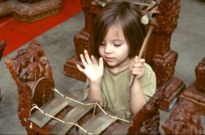 A little girl playing gamelan.