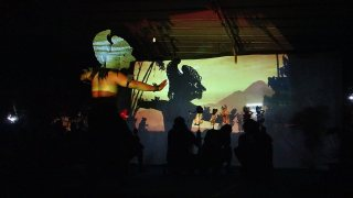 Bima dancer and puppets cast silhouettes onto a screen.