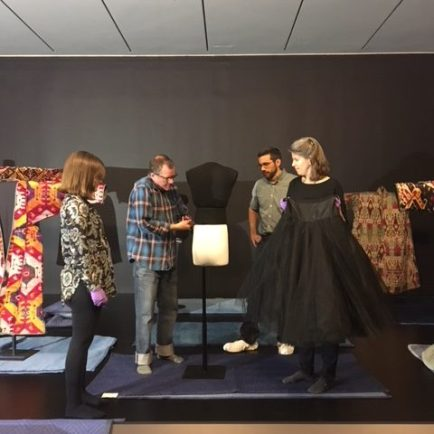 four staff members preparing a mannequin to be dressed