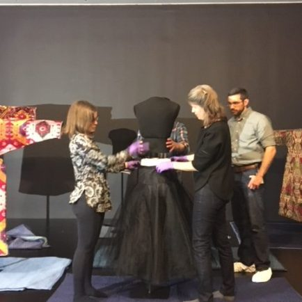 four staff members moving and adjusting a mannequin