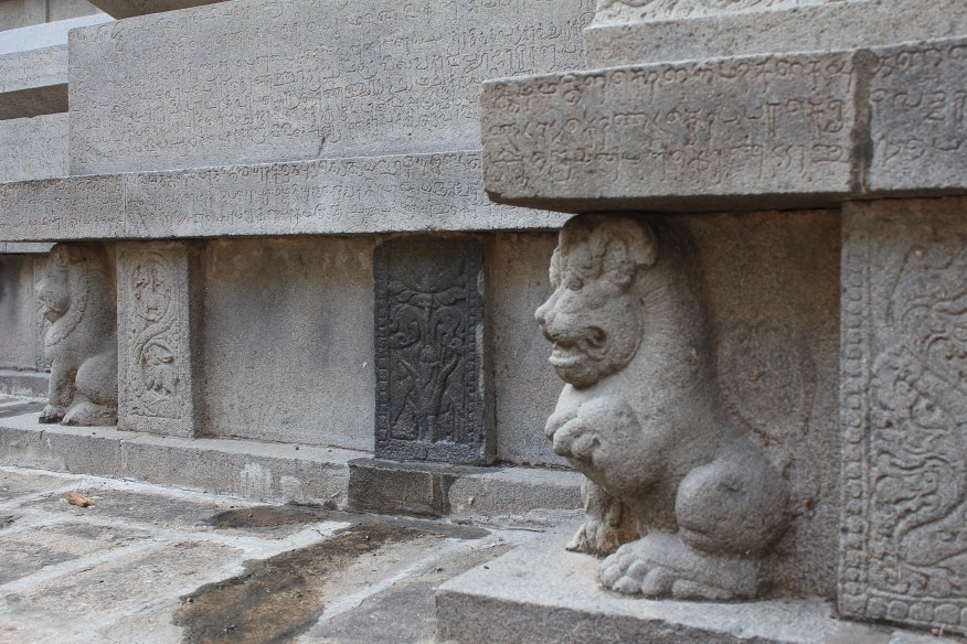 Lion sculpture supporting the base of a granite temple