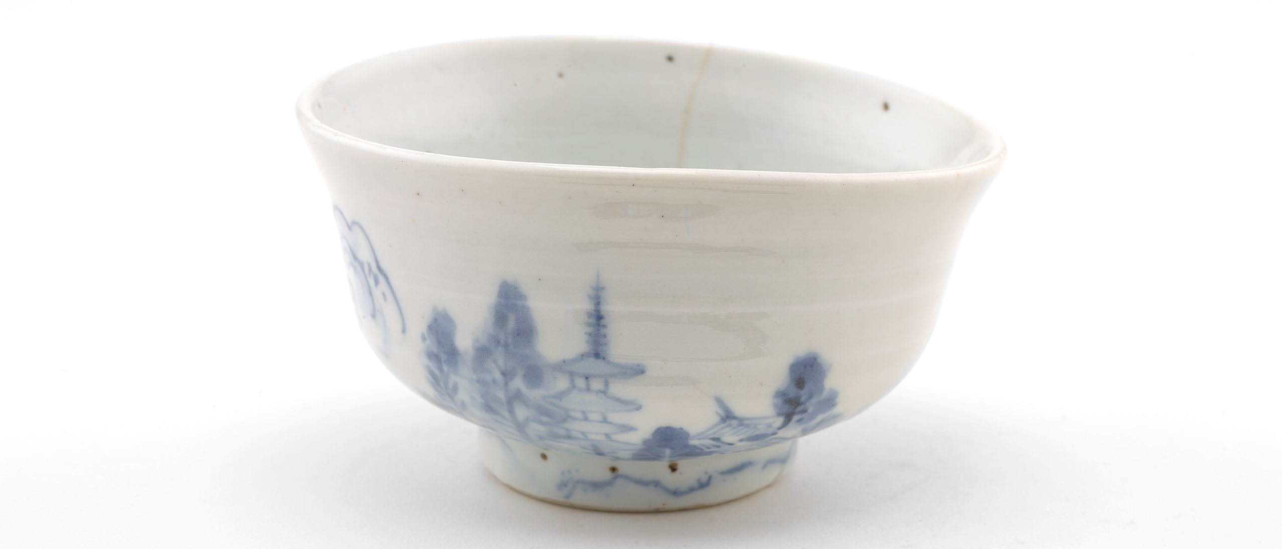 white porcelain bowl with blue design of a pagoda and landscape