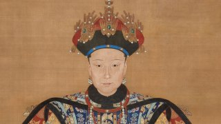 Detail from a portrait of Empress Xiaoxian, showing shoulders, head, and headgear; she is vested in ornate jewelry and robes with rich colors and intricate designs; her headdress is decorated with pearl-studded golden birds, and a slight smile shows on her face.