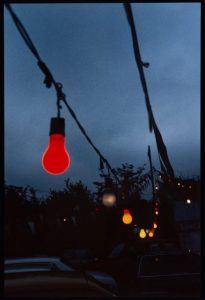 a string of red and yellow lights against a blue sky, trees and the wires dark