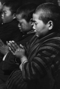 black and white photo of young men praying or meditating