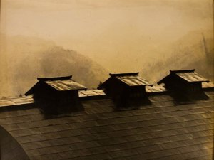 sepia-toned photo of three peaked roofs on a larger roof