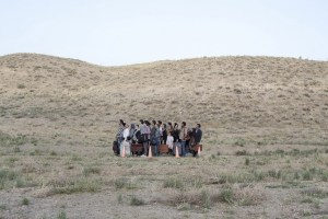 a cluster of people standing in the middle of a field holding luggage