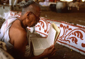A priest in a Shiva temple reads a sacred text