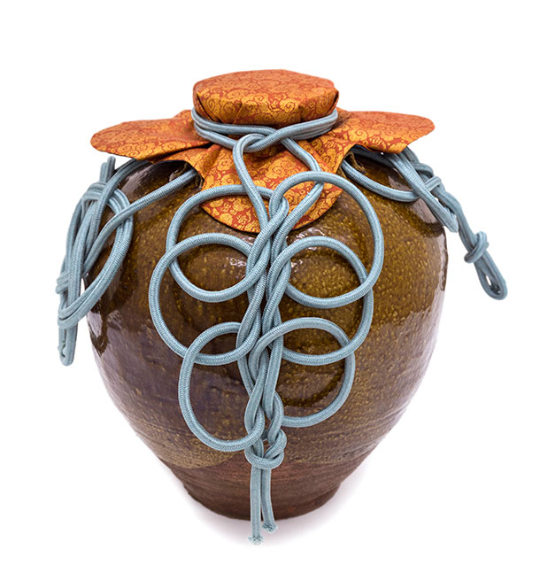 Brown tea jar dressed in orange and vermilion brocade mouth cover with cloud motif, adorned with pale blue looped and knotted cord.