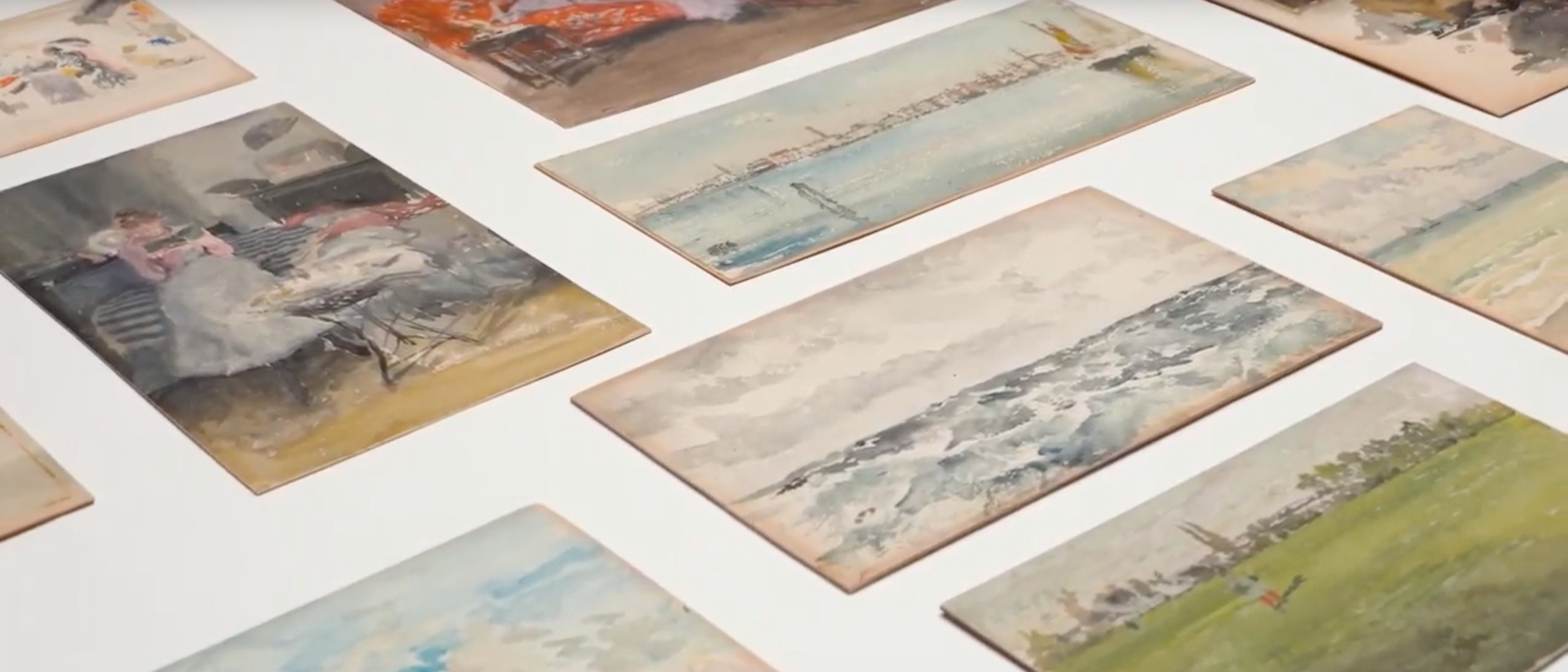 grouping of watercolor panels laid out in a grid on a white table