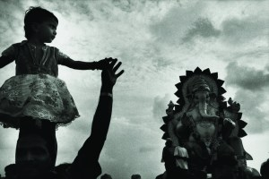 Young South Asian girl looks at elephant god statue