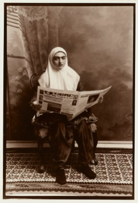 Woman with white turban reading newspaper