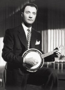 Man in suit holds mandolin.