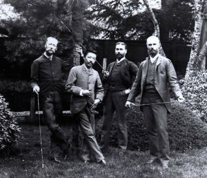 Black and white photo of four men in suits standing in a wooded area.