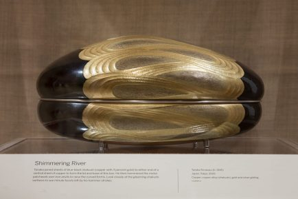 an oval container, dark at both ends, with a golden, rippling pattern on the center.