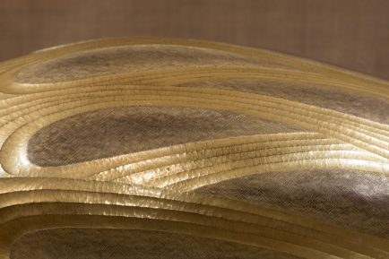 a close up of the box, showing the curving golden bands looping around darker areas with a crosshatch pattern