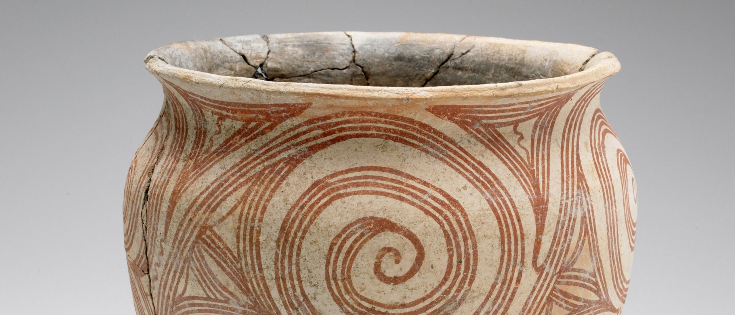 detail of an earthenware pot, showing the opening, which is slightly cracked, and the front is decorated with a reddish orange pattern of lines in a swirl.
