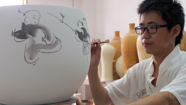 a man paints a large porcelain jar