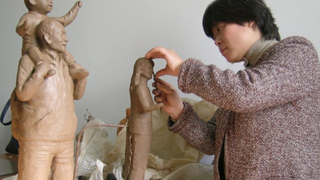 a woman sculpting figures out of clay