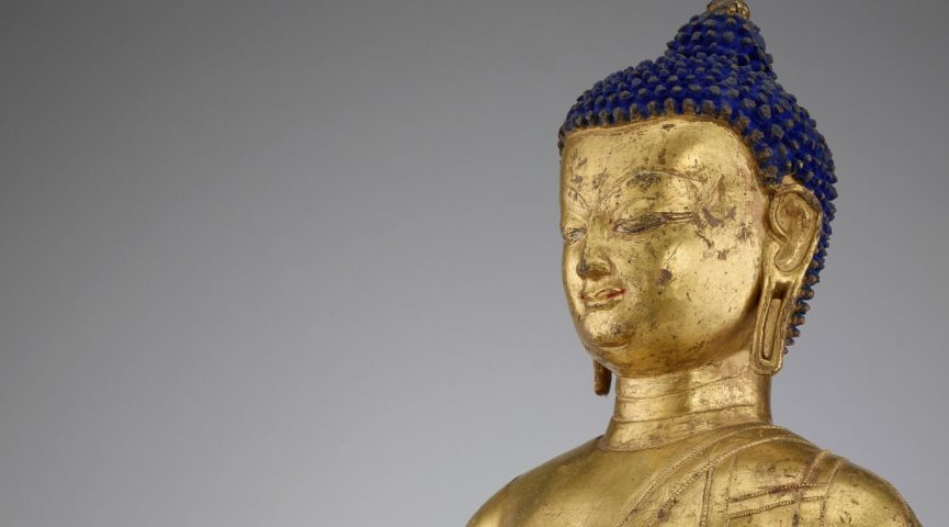 close up of a gold statue with blue hair