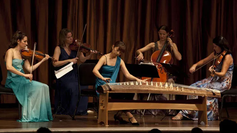photo of five women playing various string instruments, including the violin, cello and koto