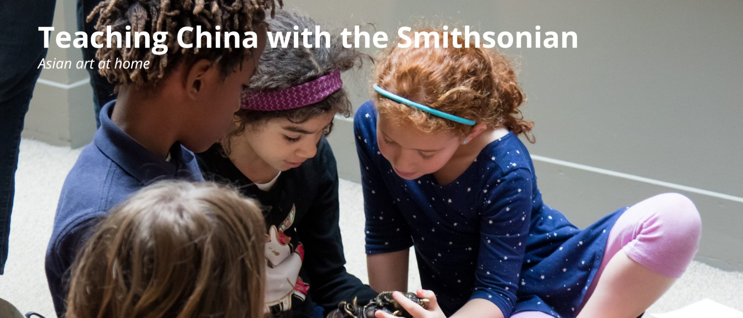Teaching China with the Smithsonian - new teacher resource. Image shows four children gathered around a small bronze object. One child holds the object in their lap.