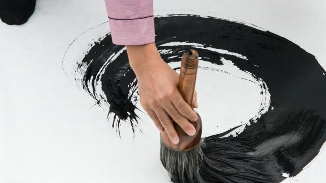 a hand holding a large brush, making a sweeping inkstroke