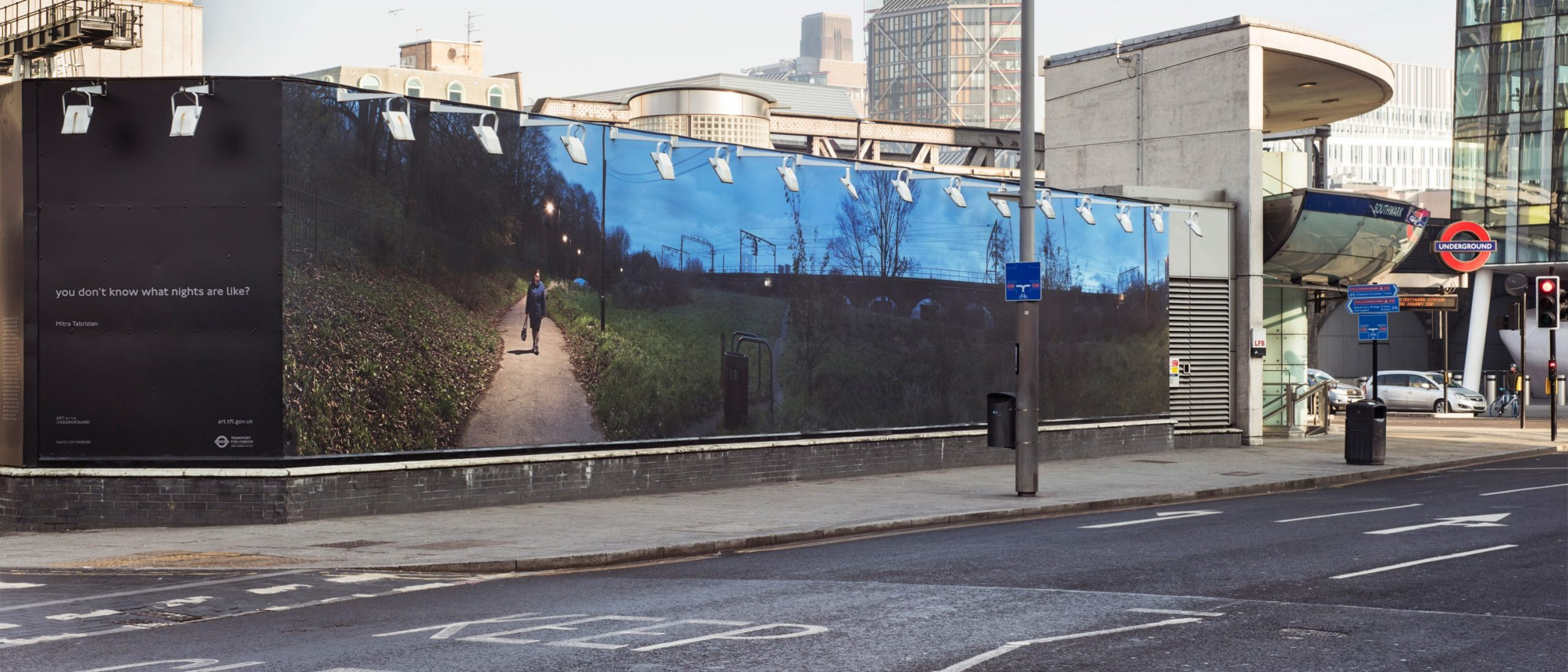 photo of a street, sidewalk and side of a building showing a mural by Mitra Tabrizian, next to a London Underground station. The mural depicts a figure walking home at late evening on a path alongside a wide green area and trees.
