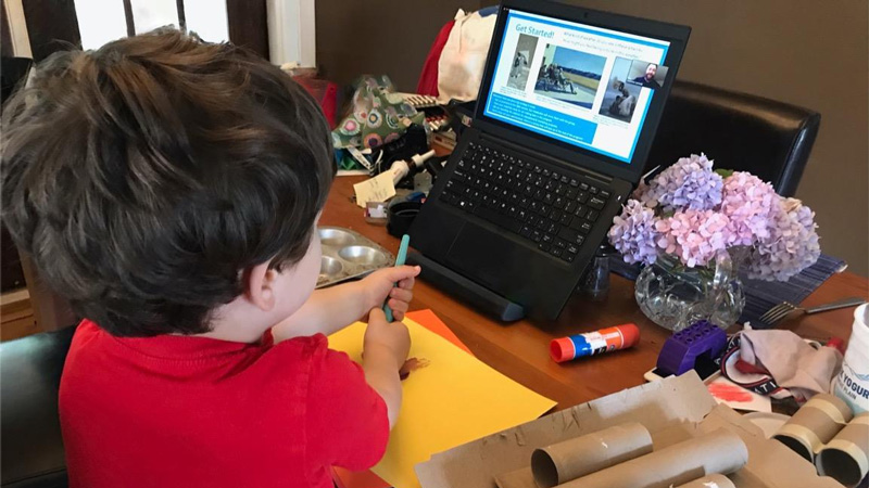photo of a child and a laptop, with crafting materials in front of them