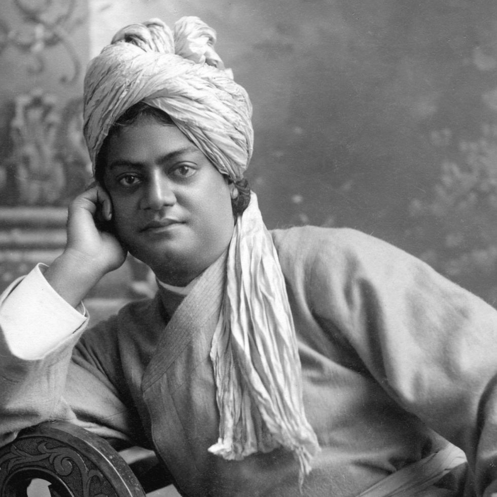 Swami Vivekananda with one hand cupping his face, his elbow rests on the back of chair on which he is seated sideways.