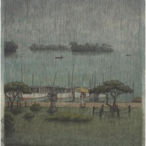 Rain falls from a gray sky on Matsushima. A figure with an umbrella walks in front of a row of boats docked in the water.
