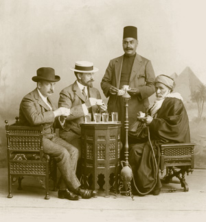 Charles Lang Freer at a table with three other men, with some glasses of clear liquid on the table and a hookah amidst them, a pyramid backdrop behind them.