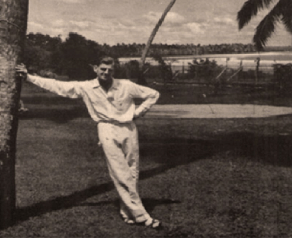 Bob Koke leaning against a palm tree with one hand and legs crossed
