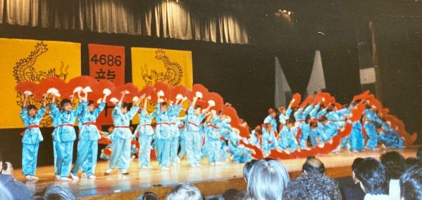 Students in blue outfits with red fans performing onstage for Lunar New Year