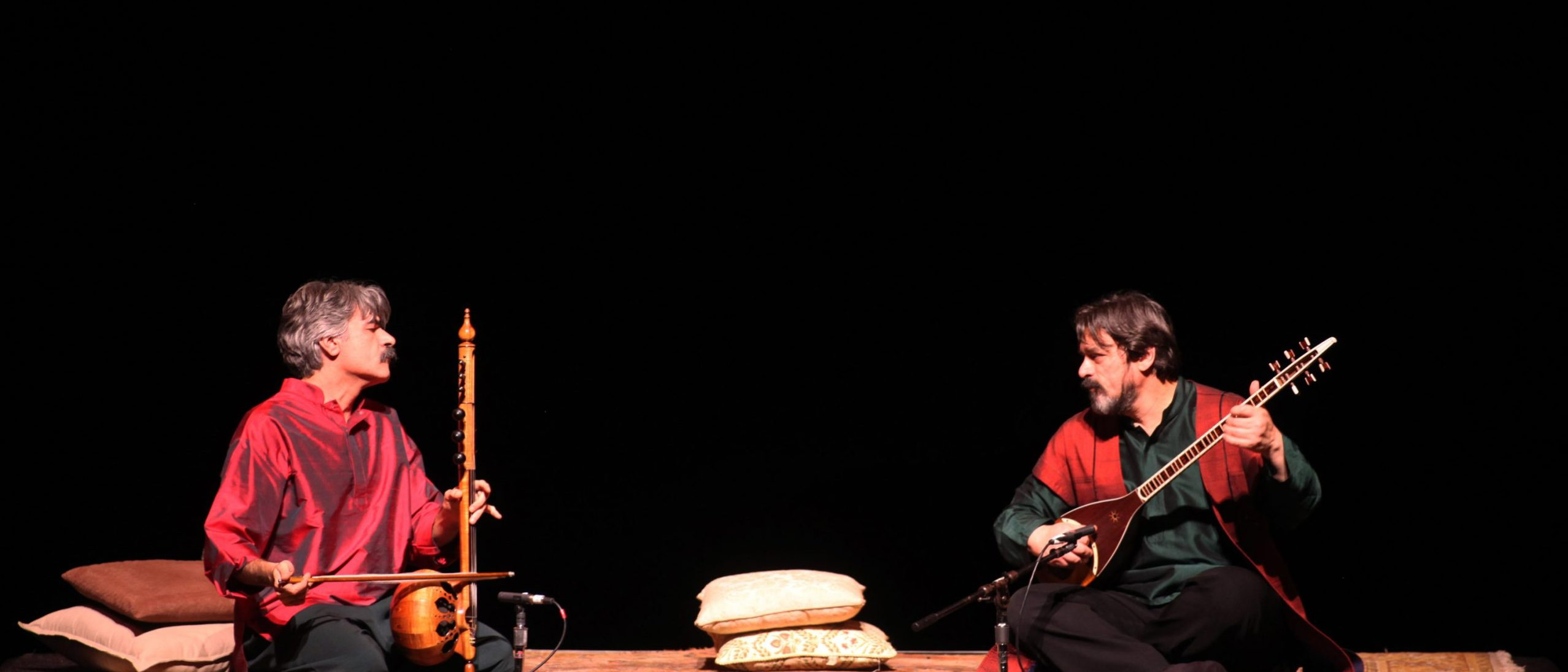 Two musicians seated on the floor, playing kamanchech (Persian fiddle) and tar (Persian lute)
