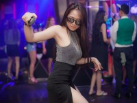 A woman on a dancefloor with a crowd behind her
