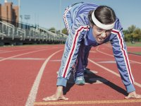 A person in a tracksuit in starting position on a track with a look of determination