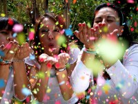 Three people outdoors blowing confetti at the camera