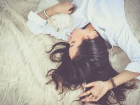 A woman cuddling a small dog while they lay on a shaggy carpet