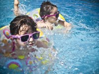 Two children in sunglasses swimming inside pool floats