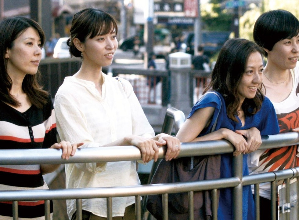 A group of four women smiling as they lean against a metal railing and look offscreen