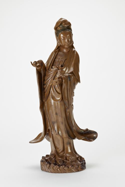 Figure of Guanyin in brown lacquer, with black texture lacquer for her hair. Her Robes drape and billow. Around the platform below her feet are scrolling waves.