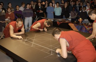 A crowd watches as monks in red continue to draw guidelines in white chalk on the table where the mandala will be created.